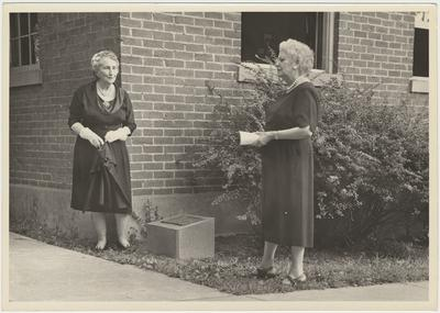 On the right is Former Students Association historian, Mrs. Pearl Day Bach. Her and another lady are dedicating a marker on the site where two Sarah K. Yancey Homes (dormitories for female students and staff) burned. The current (August 13, 1961) school and administration building they are standing by (library windows) was built by staff and students of bricks made and burned on campus Two women standing near a marker at the corner of a brick building (August 13, 1961)