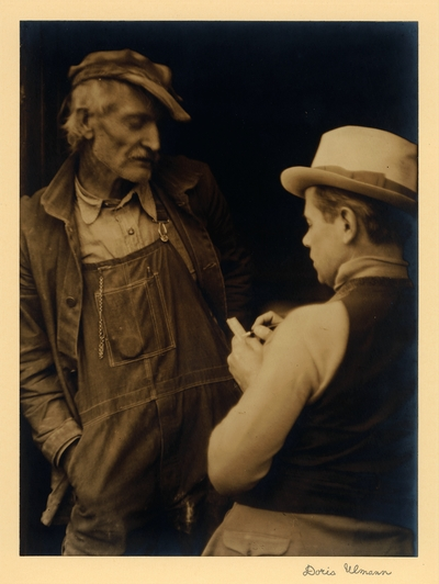 John Jacob Niles.  Elderly man in hat, coat, and overalls, and younger man (JJN) in hat and vest, taking notes