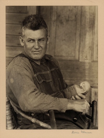 Bristol Taylor; Dulcimers, Farmer, Poet; Berea, Kentucky.  Man in overalls, seated in homemade chair, holding block of wood and carving tool