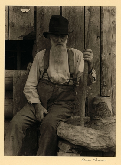 John Menders; Father of Cheevars; Cleveland, Georgia.  Elderly, bearded man in hat and suspenders, seated with big stick