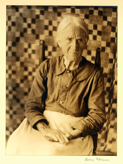 Miss Sarah Connelly; Weaver, Spinner; Brasstown, North Carolina.  Elderly woman seated in chair, with quilt hanging in background