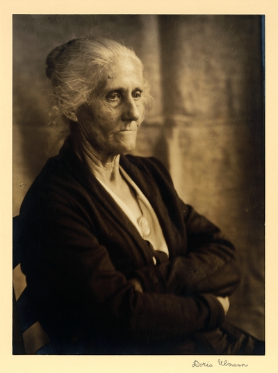 Hannah Smith; Spinner, weaver, singer; Brasstown, North Carolina.  Elderly woman seated in chair, wearing cameo, arms crossed