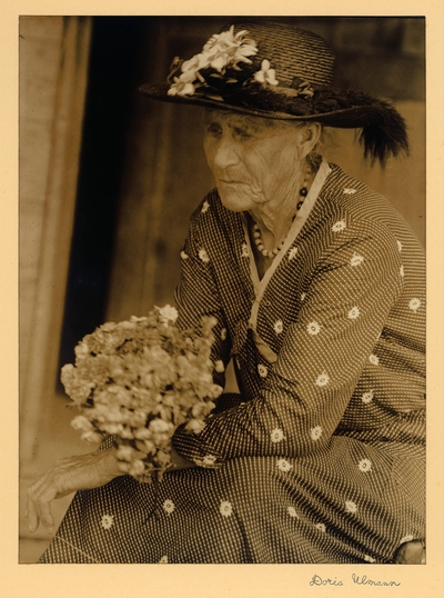 Lydia Ramsey; Sugarlands.  Elderly woman in hat, necklace, and dress, seated with flowers