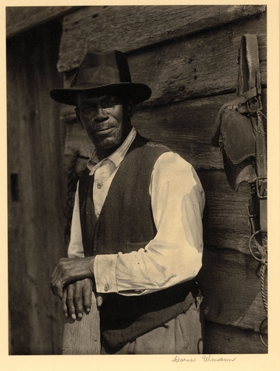 Bearded black man in hat and vest, standing with hands on post, in front of wooden building with draft horse bridle hanging on peg