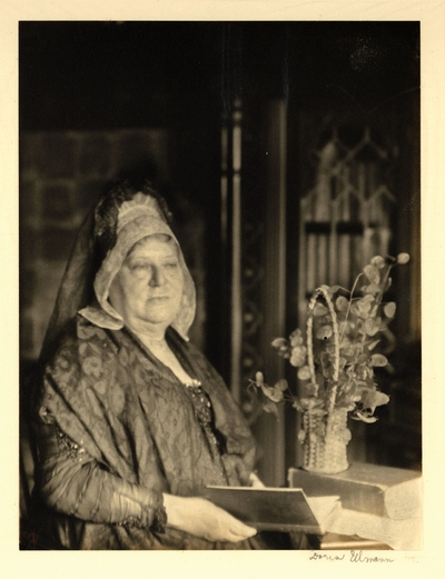 Woman in lace shawl and mantilla, seated beside plant in basket, holding book.  Ca. 1918-25