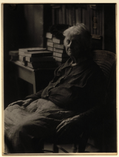 Elderly woman in blouse and skirt, seated in chair, with bookshelf and table with books and hat in the background