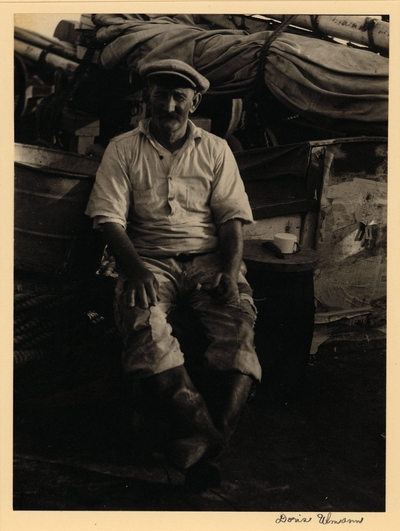 Man with mustache, in hat, ragged pants, and boots, seated with mug on a barrel beside him