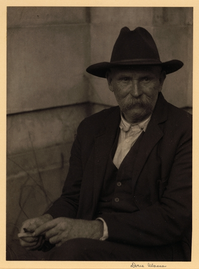 Covey Odhom, Tanner, Luther, Tennessee. Elderly man with mustache, in hat and suit, seated in corner, whittling