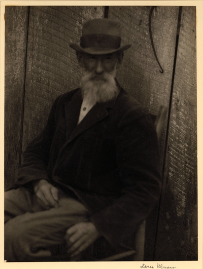 Elderly, bearded man in hat and coat, seated in chair