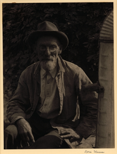 Elderly, bearded man in hat, glasses, and shirt, seated beside water tank with spigot showing