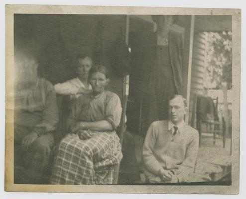 Patients, unknown: Unintelligent looking chap seated at right has trachoma--has not seen for years and sings for a living. Uncle John and Aunt Sis to the left. taken at Pine Mountain in 1916 or 1917