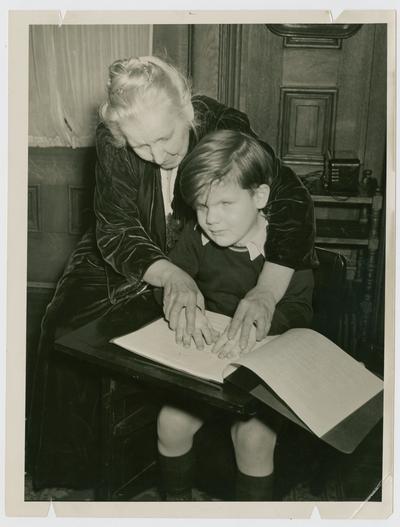 Linda Neville teaching David Devary to read braile
