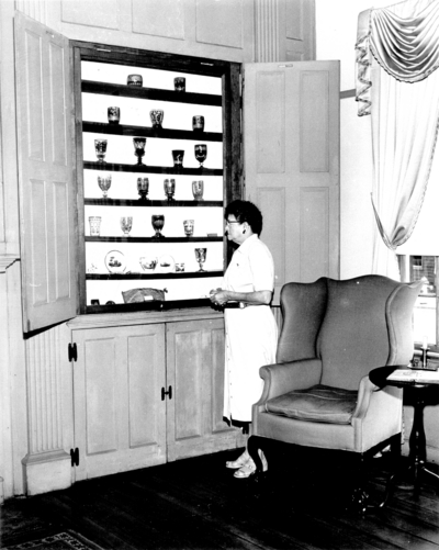 Photograph by the Lexington Herald-Leader an interior view an unidentified female looking at goblets in the library at the Ephraim McDowell House. 8x10