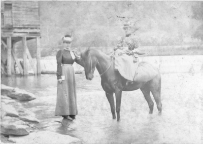 Two unidentified women, one is on a horseback.  Both are standing in a creek near waterfall.  The horse is laden with supplies. Bromide