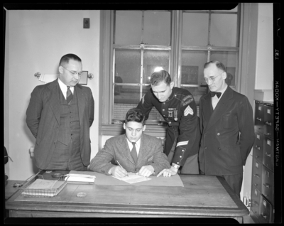 United States Marine Corps, recruiting office; group of men                             standing next to a desk as a young man signs paperwork