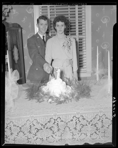 Mr. & Mrs. Perkins; wedding; portrait of wedding couple                             ready to cut their cake; Lowell Perkins (groom); Ann Kaninberg                             (bride)