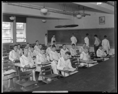 Moorhead College; classroom, interior; group of naval (navy)                             recruits (students) sitting at desks and working at the chalk                             board