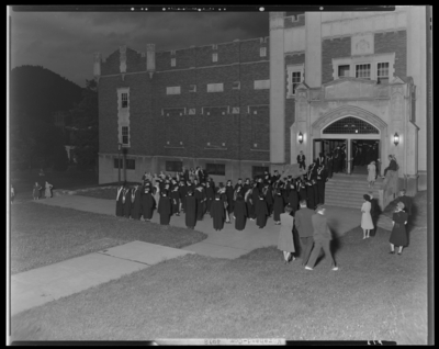 Moorhead College; graduation; exterior of unidentified building;                             graduates lining up to enter building