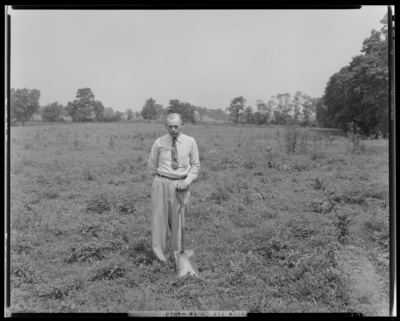 Irving Air Chute; digging dirt; man in a field holding a                             shovel
