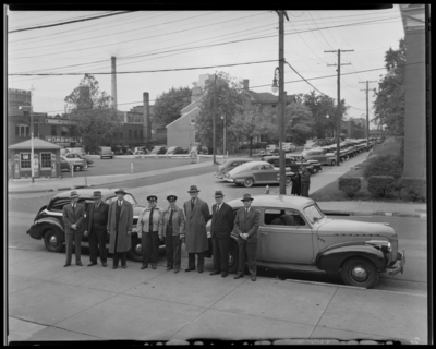 Lexington Yellow Cab, 150 North Limestone; group for first women                             drivers; two women drivers in uniform standing with a group of men in                             front of cab cars; Walnut Street & unidentified cross street;                             sign for Wombell's Automotive Parts can be seen