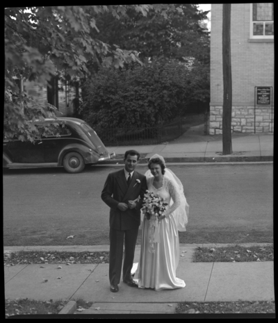 Robinson Wedding (two weddings); West Maple, Nicholasville);                             portrait book; bride and groom standing on the sidewalk for a                             portrait