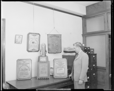 Kentucky Utilities Company (167 West Main Street); man standing                             next to trophies