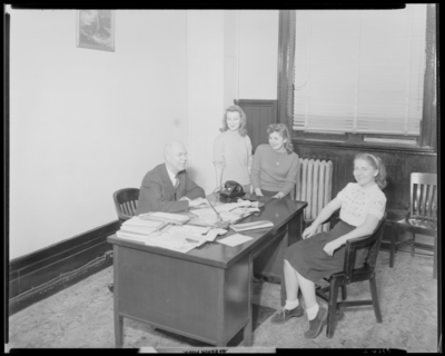 Georgetown College; group gathered around a desk