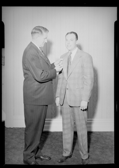 National Life & Accident Insurance Company; Phoenix                             Hotel; interior; Luncheon; two men standing together; man placing a pin                             on the other man's lapel