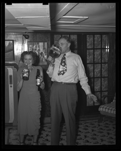 R.J. Long (Lafayette Studios); Thanksgiving Dinner; man and woman                             drinking out of bottles and a large glass