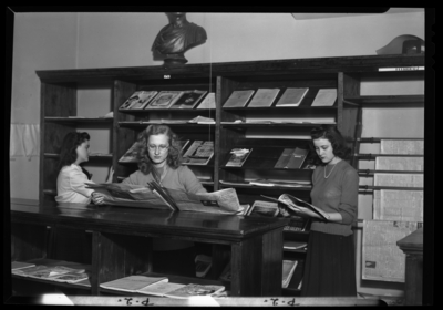 Georgetown College; library; interior; students gathered around                             the periodicals section