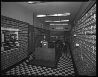 Thom McAn Shoe Company, 114 West Main; interior; man being waited                             on