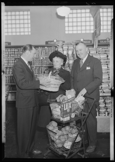 Kroger Store; 726 East Main; interior; woman standing beside her                             shopping basket, two men presenting woman a basket of grocery                             coupons