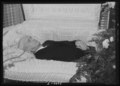Chas P. Perkins; corpse; open casket surrounded by                             flowers