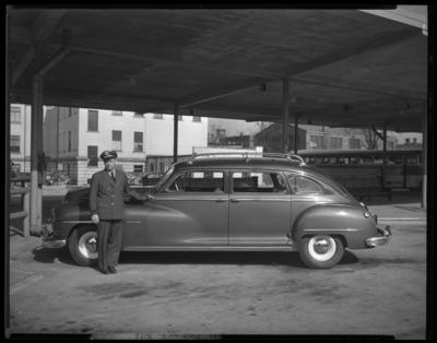 All-American Tour; Bus Terminal; exterior; chauffeur standing                             next to car