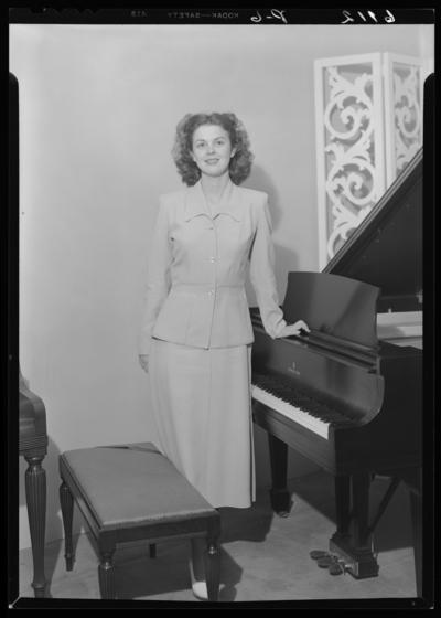 Mrs. J.B. Brookshire (Raymondville, Missouri); interior; woman                             standing next to piano