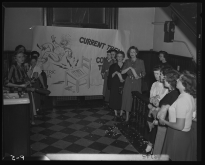 Belle of the Blue; Georgetown College; interior; group of women                             standing in front of banner with drawing of electric chair