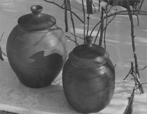 Two ceramic pots with lids sitting in snow, pieces of John Tuska's Alfred University graduate work
