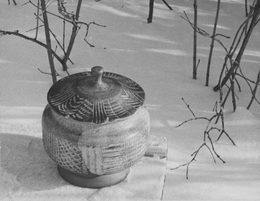 A ceramic pot with a lid sitting in snow, a piece of John Tuska's Alfred University graduate work