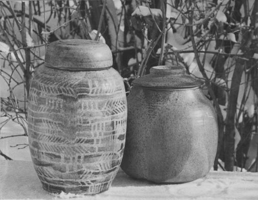 Two ceramic pots with a lids sitting in snow, pieces of John Tuska's Alfred University graduate work