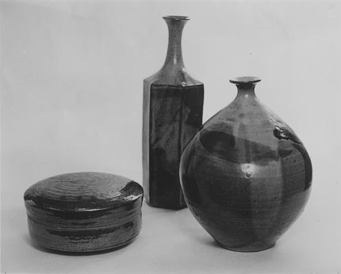 Two ceramic bottles and a round shaped box with a lid by John Tuska. One of the bottles has a hexagonal shaped body and the other is round