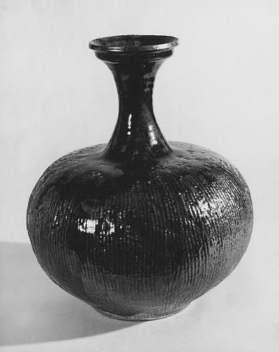 A ceramic vase with vertical lines by John Tuska