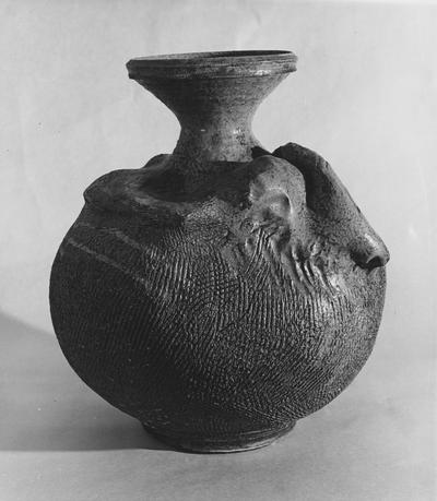 A ceramic vase with a round body and cross hatched lines by John Tuska