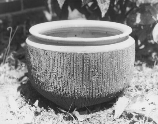 A ceramic pot with a round body and vertical lines by John Tuska
