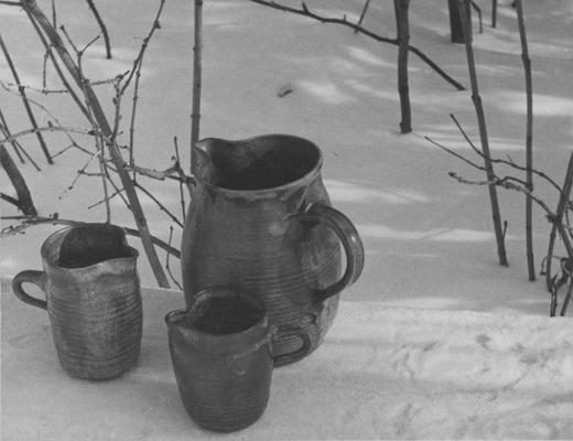 Three ceramic pitchers sitting in snow, pieces of John Tuska's Alfred University graduate work