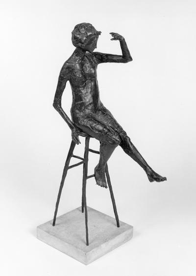 A bronze sculpture of a female nude mounted on travertine marble entitled