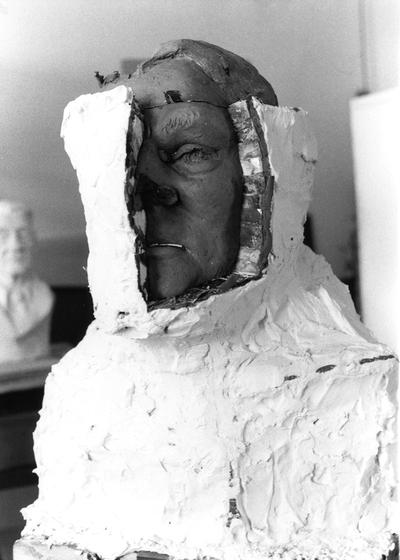 An image of plaster being removed from a John Sherman Cooper bust by John Tuska