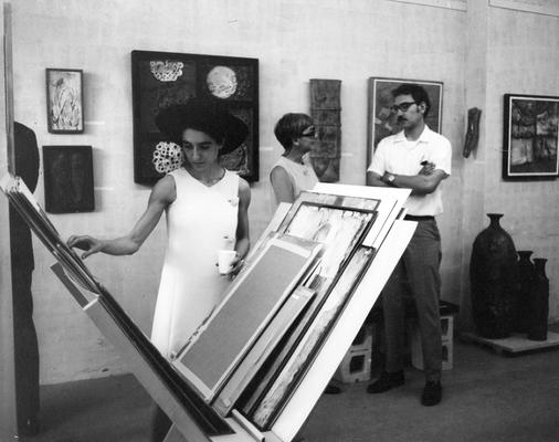 Three unidentified persons viewing art at an unknown exhibit. This photograph was taken by Shirley W. Schweet