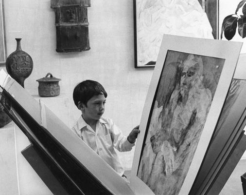 A young boy viewing art at an unknown exhibit. This photograph was taken by Shirley W. Schweet