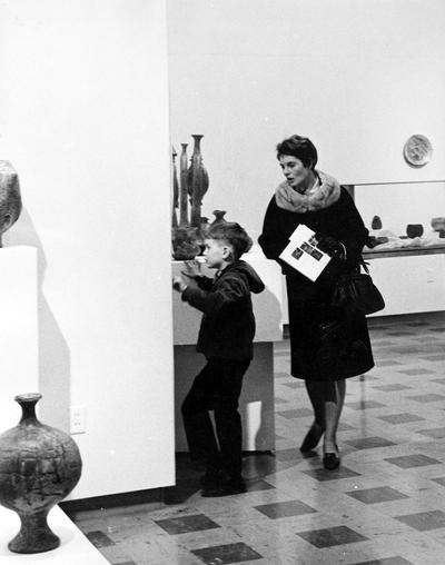 A young boy and woman viewing art in an exhibit entitled