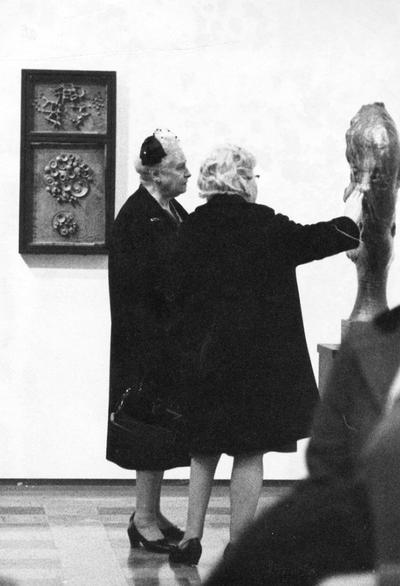 Two women viewing a ceramic vessel at an exhibit entitled